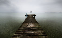 Woman standing on a wooden jetty. Woman on a pier on the lake greeting the sea with arms wide open. Royalty Free Stock Images