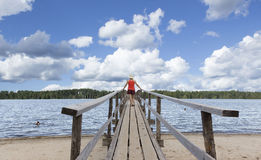 Woman standing on a wooden pier watching kids swimming. Royalty Free Stock Image