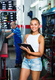Woman standing and writing down data at car service Stock Image
