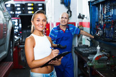 Woman standing and writing down data at car service Stock Photos