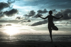 Woman standing at yoga pose on the beach during an amazing sunset in cold gray-blue tones. Royalty Free Stock Image