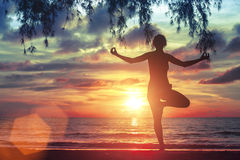 Woman standing in yoga pose on the beach during the amazing sunset. Stock Photography