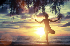 Woman standing at yoga pose on the beach during sunset. Royalty Free Stock Photos