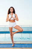 Woman standing in yoga pose on one leg Stock Photography