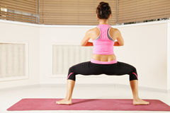 Woman standing in yoga pose rear view Royalty Free Stock Photo