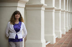 A Woman Stands Amid Spanish Revival Style Architecture. A Smiling Woman Stands Amid the Columns of Spanish Revival Style Architecture stock images