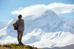Woman stands with backpack at mountains royalty free stock photos