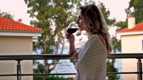Woman stands on balcony and drinks wine stock video