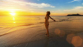 Woman stands on the beach welcoming the dawn. Royalty Free Stock Photos