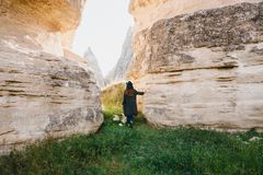The woman stands between beautiful rocks and admires the landscape in Cappadocia in Turkey Royalty Free Stock Image