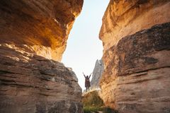 The woman stands between beautiful rocks and admires the landscape in Cappadocia in Turkey. Raises his hands up. Freedom Royalty Free Stock Images