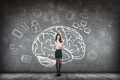 Woman stands beside big drawn brain stock images