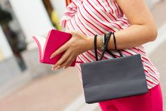 A woman stands with a black paper bag in her hands. Shopping concept. Space for text on the bag stock photos