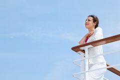 Woman stands on board of ship and rests her hands Stock Image