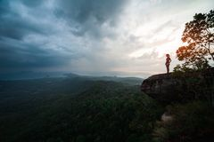Young woman hiker. Woman stands on the cliff and enjoys the valley view during sunset royalty free stock photo