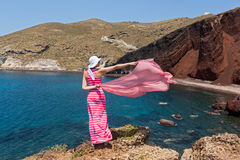 Woman stands on a cliff and looks at the red beach Royalty Free Stock Image