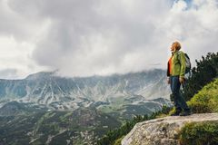 Woman stands on the cliff and looks at the tops Stock Image