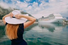 Woman stands on cruise liner background. Young woman in hat stands on cruise liner background, rear view royalty free stock images