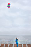 Woman stands on cruise liner deck and flies kite Royalty Free Stock Images