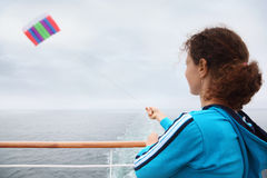 Woman stands on cruise liner deck and flies kite Stock Photo