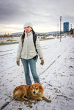 Woman stands with dog on the road that cover with snow. Chile, Punta Arenas Royalty Free Stock Images