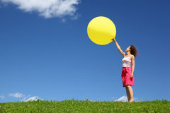 Woman stands on grass and starts inflatable ball Stock Image