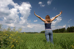 woman  stands on a green field Royalty Free Stock Image