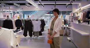 Happy woman stands with a handbag in a clothing store and looks at the camera, shopping