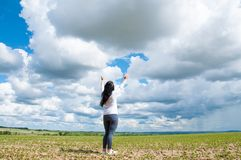 A woman stands with her arms raised and prays to God. On a green field in summer. stock photography