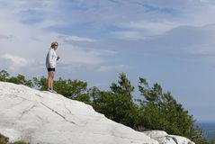 A Woman Stands High Above the Wilderness. Royalty Free Stock Photos