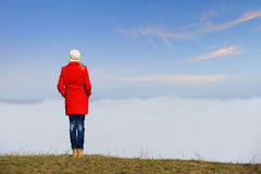 Woman stands on a hill above the clouds Stock Photos