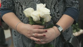 Woman stands and holds bouquet of five white roses stock video