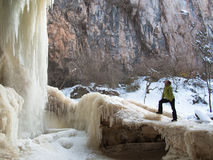 A woman stands on the ice near a waterfall Stock Photos