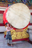 A woman stands beside a large drum Royalty Free Stock Image