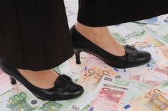 Woman stands on money Royalty Free Stock Images