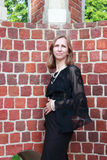 A woman stands near the brick wall Royalty Free Stock Images