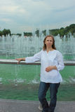 A woman stands near a fountain Royalty Free Stock Photography