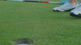 Final blow in a golf. Woman stands near the golf ball on green lawn and makes the final blow over the ball with putter. The ball falls into a hole and game stock footage
