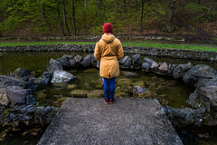 Woman stands near lake in city park and thinks. Woman stands alone near lake in city park and thinks Stock Photos
