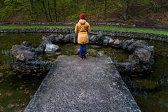 Woman stands near lake in city park and thinks. Woman stands alone near lake in city park and thinks Stock Image