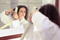 Woman stands near mirror and dries hair Royalty Free Stock Images