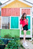 Woman Stands Near Multicolored Wooden House royalty free stock photography