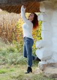 A woman stands near the old house with thatched roof. Hands raised up and smiling royalty free stock image