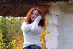 A woman model stands near the old house in a white knitted sweater and holds hands near the head royalty free stock photography