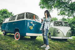 Woman stands near retro vans and lookin something on phone. In rainy weather Royalty Free Stock Photography