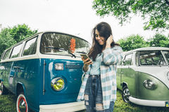Woman stands near retro vans and lookin something on phone. In rainy weather Royalty Free Stock Image