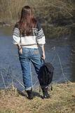 Woman stands near river, soft focus background Stock Photo