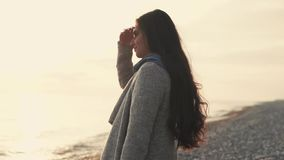 Woman stands near the sea, lady with long hair enjoys beautiful natural scenery stock footage