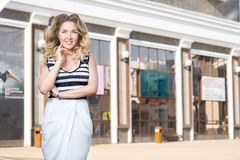 Woman stands near stores. A young woman stands near stores Royalty Free Stock Image