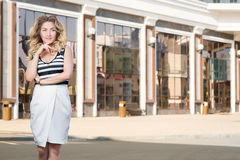 Woman stands near stores. A young woman stands near stores Royalty Free Stock Photo